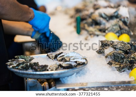close-up of the process of shucking oysters at the restaurant, shallow DOF on plate - stock photo