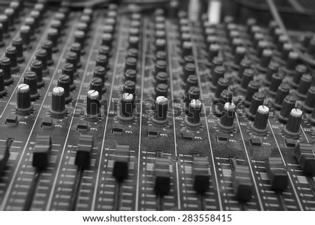 Close up of the rows of knobs and sliders on an analogue mixing console, in black and white
