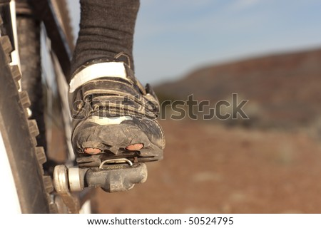 Close up of the shoe of a person riding a mountain bike in a desert landscape. Horizontal shot. - stock photo
