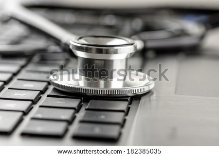 Close up of the silver metal disk of a medical stethoscope on a laptop keyboard, conceptual of online healthcare. - stock photo