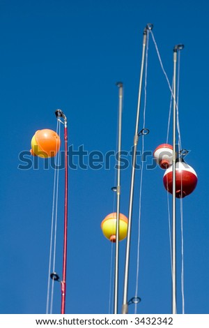 Close-up of the tips of several fishing poles shot against a blue sky. - stock photo