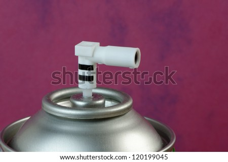 Close up of the top of an aerosol can showing the spray nozzle. 36 mp image against pink - stock photo
