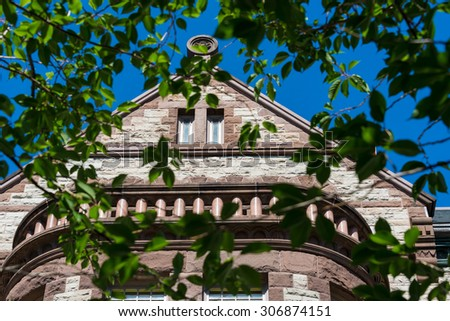 Close-up of the top triangular structure of Victoria university building seen through branches. Victoria University is a college of the University of Toronto, founded in 1836  - stock photo