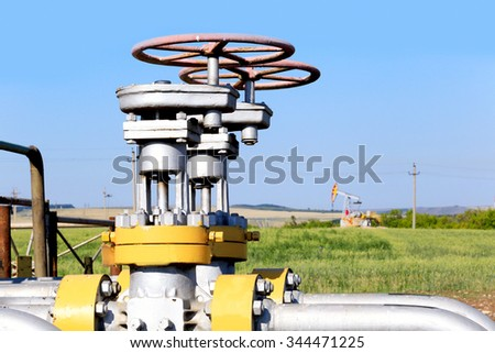 close-up of the valve plug an oil pipeline in the field on a sunny summer day - stock photo