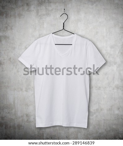 Close-up of the white t-shirt on the clothes hanger. Concrete background. - stock photo