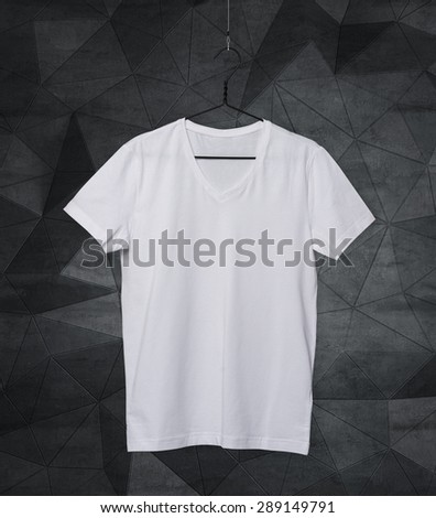 Close-up of the white t-shirt on the clothes hanger. Modern background. - stock photo