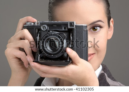 Close -up of the young woman having control over the antiquarian camera.