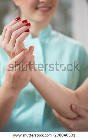 Close-up of therapist exercising with patient's arm - stock photo