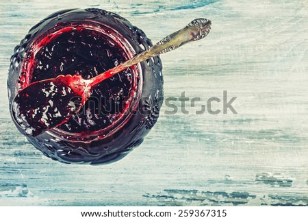 Close up of thick sweet strawberry jam with old spoon. Top view of fruity jam. - stock photo