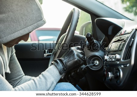Close-up Of Thief Using Tool To Steal Car - stock photo