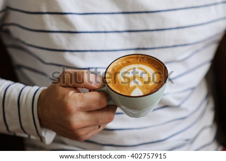 Close-up of thoughtful man holding cup of coffee while sitting at the desk. Casual style, stripes on t-shirt. - stock photo