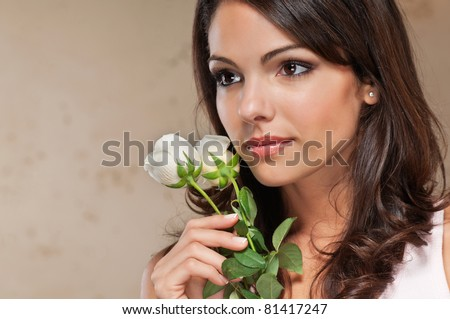 Close-up of thoughtful pretty young woman holding white roses