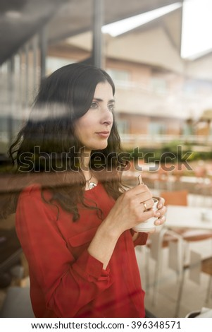 Close-up of thoughtful wavy haired woman standing behind cafe's window while holding cup of coffee