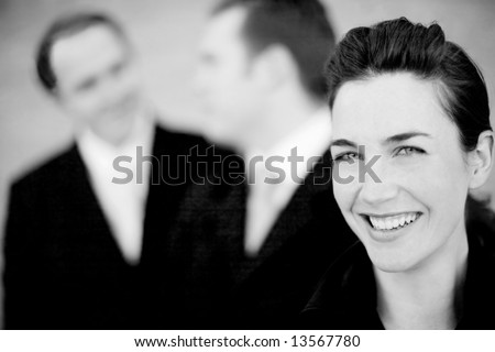 close up of three attractive businesspeople smiling and talking - stock photo