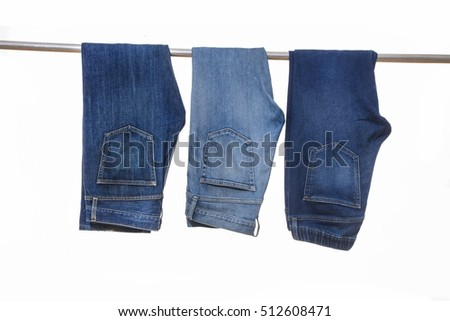 close up of three blue jeans on hanger