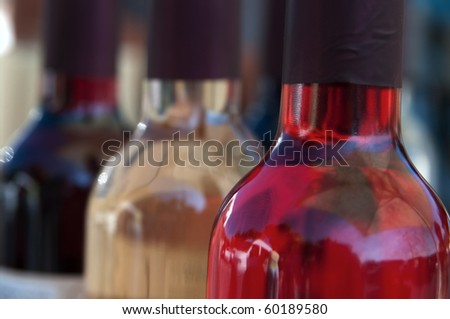 Close-up of three bottles of wine with perspective effect - stock photo