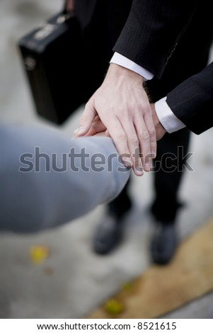 close-up of three business men's hands on top of each other - stock photo
