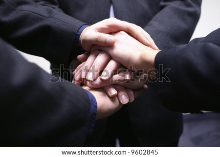 close-up of three businessmen hands on top of each other - stock photo