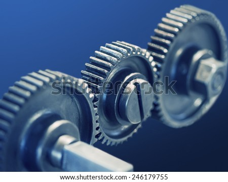 Close up of three cog wheels on blue background