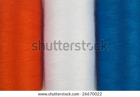 close up of three colored sewing spools - stock photo