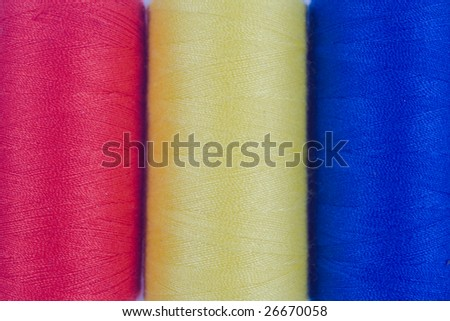 close up of three colored sewing spools