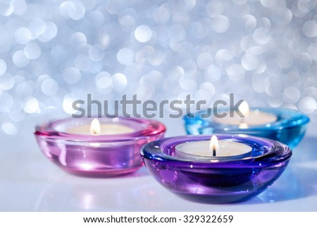 Close up of three colorful Christmas candles on a blur background with bokeh. Selective focus.