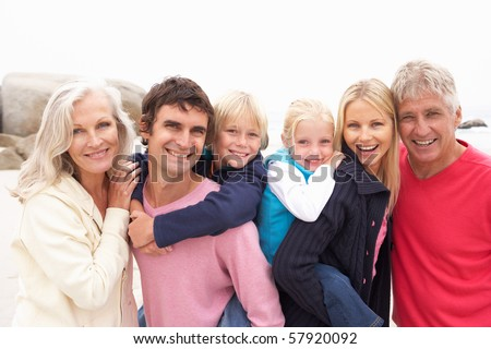 Close Up Of Three Generation Family On Winter Beach - stock photo