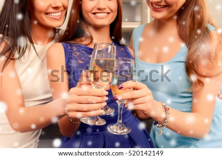 Close up of three happy smiling women holding glasses with shampagne.