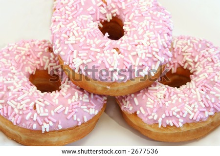 close up of three iced donuts with sprinkles - stock photo