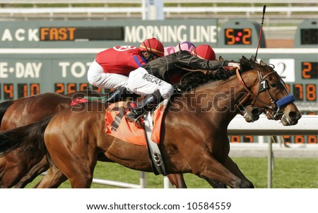 Close-Up of Three Jockeys Running Neck and Neck in a Thoroughbred Horse Race - stock photo