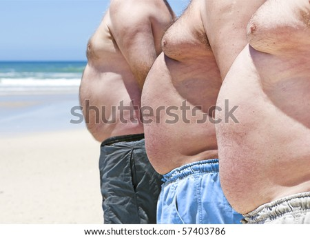 Close up of three obese fat men on the beach showing their unhealthy bellies - stock photo