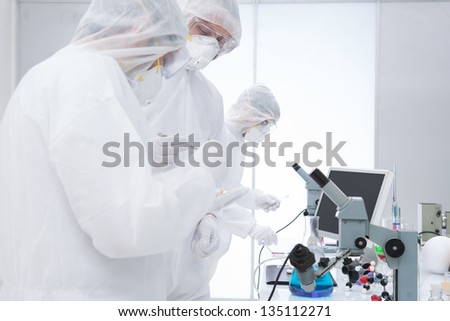 close-up of  three people manipulating  lab tools in a chemistry lab around a lab table - stock photo