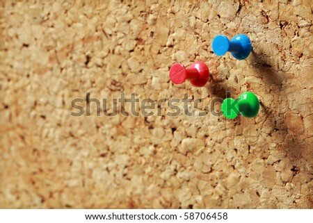 Close up of three push pins on a cork message board - stock photo