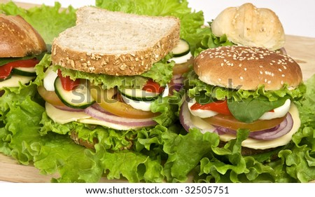 Close up of three veggie burguers containing: soy meat, cheese, lettuce, tomato, cucumber, onion, egg. - stock photo