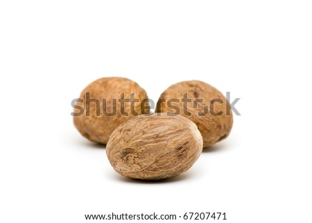 Close up of three whole nutmegs on white background - stock photo