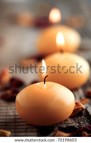 Close up of three yellow candles with shallow focus