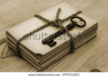 Close up of tied with twine bundle of old paper with old rusty weathered metal door keys on old rustic wooden table background, sepia - stock photo