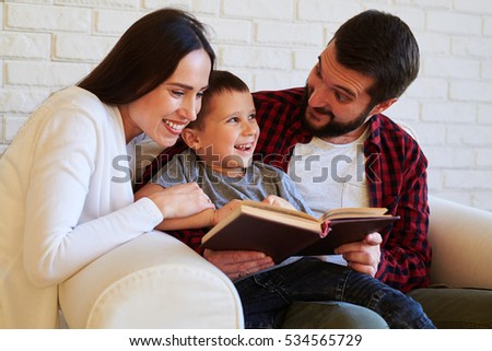 Close-up of tight-knight family. Spending time together. Parents supporting a child while reading, positive achievements of �° kid