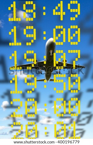 Close up of times of departure or arrival on blue sky with aircraft - stock photo