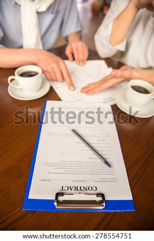 Close-up of to businessmen sitting at wooden table with coffee and signing the contract. - stock photo