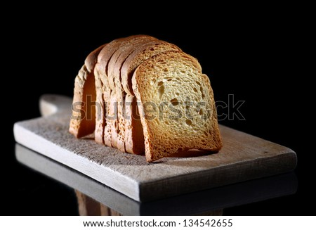 Close up of toasted white bread in slices on cutting board over black background - stock photo