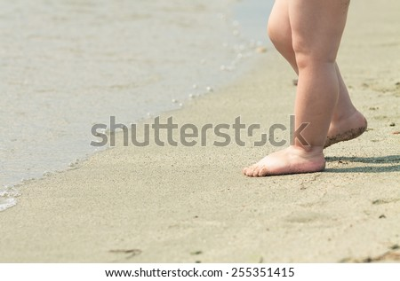 Close up of toddler's feet at the edge of the water on a beach. Photo with untraditional color rendering for artistic look - stock photo