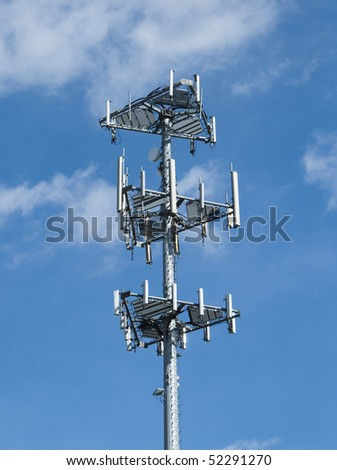 Close up of top of cell tower against blue sky - stock photo