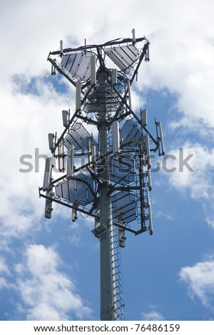 Close up of top of cell tower against blue sky with fluffy clouds