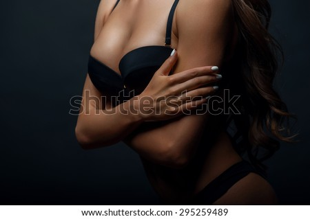 Close up of torso of attractive woman in black underwear. She crossed her hands shyly. Isolated on black background