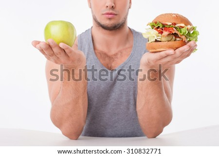 Close-up of torso of man sitting at the table. He is choosing between fruit and hamburger. The man is holding it in his hands. Isolated on background - stock photo
