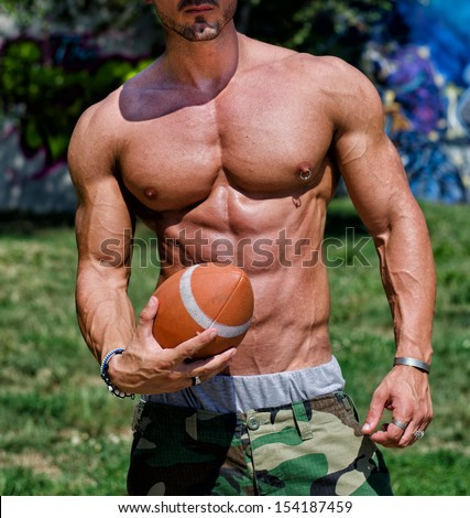 Close-up of torso of very muscular man naked with football in his hand, outdoors - stock photo