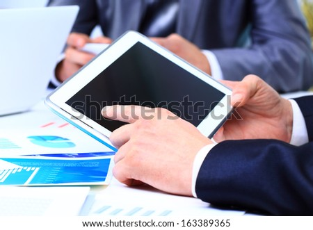 Close-up of touchpad in businessman hands during meeting - stock photo
