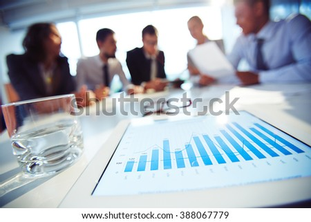 Close-up of touchpad with graphics on the table with people in the background - stock photo