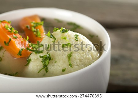 Close up of traditional chicken Soup with dumplings on a rustic wooden table - stock photo